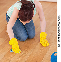 Attractive red-haired woman cleaning the floor while...