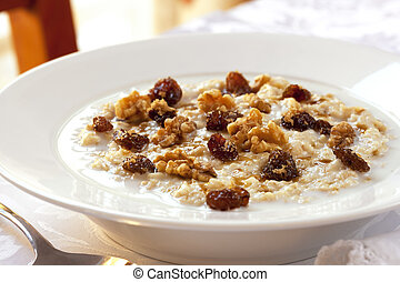 Oatmeal - Bowl of oatmeal topped with raisins, walnuts and...