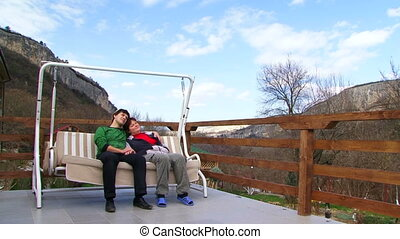Couple on vacation in the mountains - Man and woman sitting...