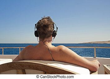 Person relaxing on a boat with headphones - Person...