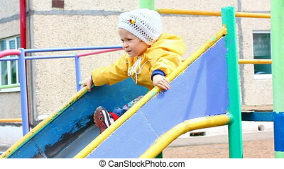 cute little girl in yellow on slide - slow motion