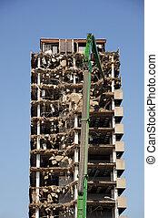 Demolishing highrise building - Green crane demolishing a...