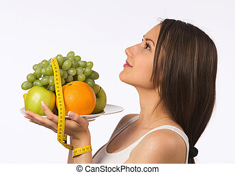 Young woman holding a plate with fresh fruit and tape measure