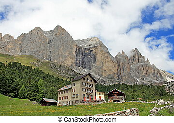 alpine hut at the foot of the mountain in Val di Fassa