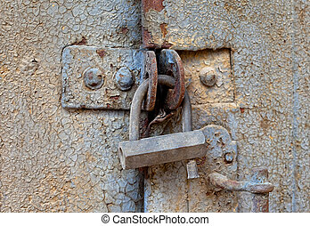 Old padlock on a metal door