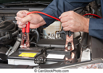 battery cables - A car mechanic uses battery jumper cables...
