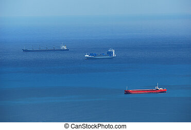 Cargo ships in blue sea - Three cargo ships in blue sea