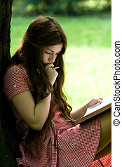 girl studying in the park - attractive girl with long hair...