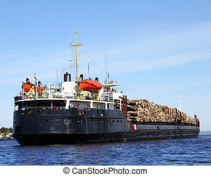 cargo of logs - The barge with cargo of logs leaves in sail