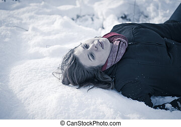 Frozen to death concept Young female model lying on snow