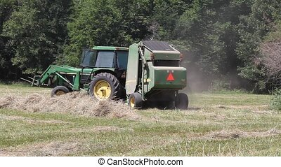Now The Baler Takes Over - After the rake puts the hay into...