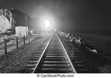 Train tracks at night with a train coming down the tracks....