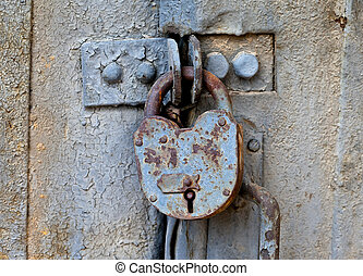 Rusty padlock on an old metal door