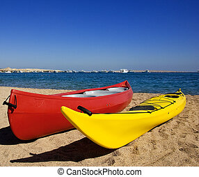 Canoes on a beach - Two colourful canoes on a beach in a...