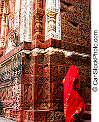 A lady in a red sari climbs the stairs to enter an ancient...