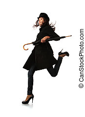 Fashion model in black with umbrella running over white background