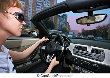 Young woman driving convertible car in city. Wide angle view.
