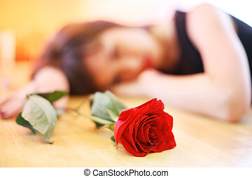 Lonely young woman with red rose. Shallow DOF, focus on...