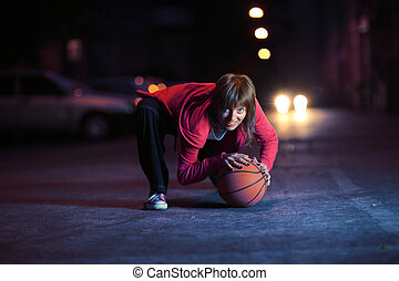 Young woman with basketball ball on night street