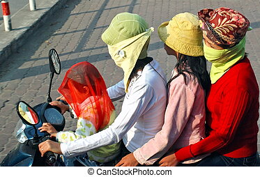 smog - four female moped riders with face masks