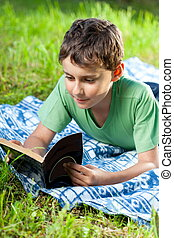 Child reading a book outdoor - Portrait of a boy reading a...