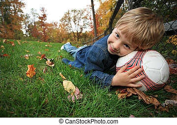Boy lying on green grass with soccer ball under his head
