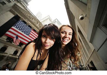 Two young women near New York Stock Exchange. WIde angle...