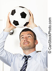 young businessman in office with ball in the hands