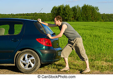 The man pushes the car in the field