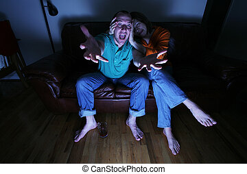 Husband and wife watching TV at home