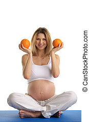 Pregnant woman practicing yoga and keeps oranges isolated on...