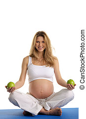 Pregnant woman practicing yoga and keeps apples isolated on...