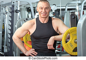 champion - Mature sporty man in the gym centre.
