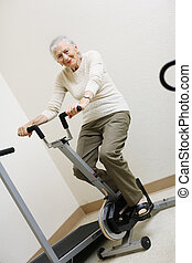 Senior woman pedaling on stationery bike