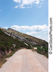 Mountain Gravel Road - Emtpy gravel road through mounatin...