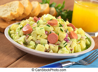 Fresh potato salad made of potato, cucumber, red onion and chives with a mayonnaise dressing and sausage slices with orange juice and baguette slices in the back (Selective Focus, Focus one third into