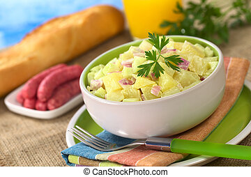 Potato salad made of cooked potatoes, red onions and cucumber, seasoned with a mayonnaise dressing and garnished with a parsley leaf with sausages, baguette and orange juice in the back (Selective Foc