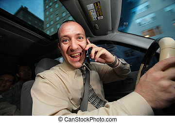 Businessman driving in car and talking on cell phone.