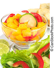 Fresh salad of mango, red bell pepper, cucumber and lettuce (Selective Focus, Focus on the cucumber slice in  the bowl)