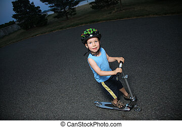 Little boy riding scooter outdoors