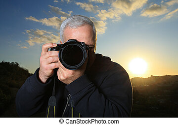Nature photographer taking photo at sunset