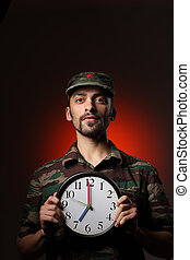 Get up - Portrait of a soldier holding clock set at 7AM