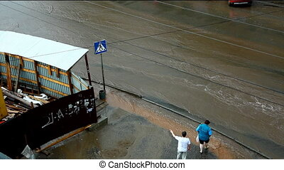 thunderstorm in city - peoples walk on road with flood