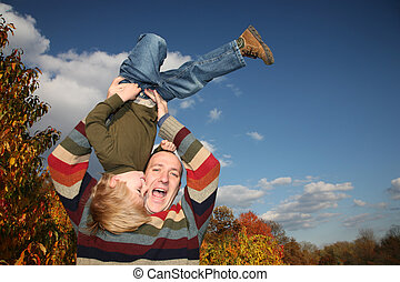 Happy father lifting son upside down over blue sky
