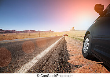 Car on highway leading to the horizon - Car on a side of...