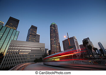 Bus speeding in downtown Los Angeles at twilight