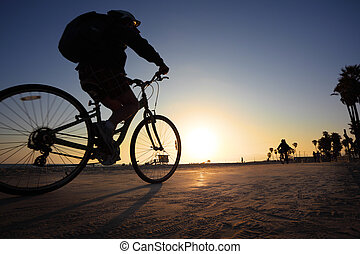 Biker silhouette riding along beach at sunset