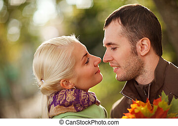 Young couple in love outdoors in park, close-up, shallow DOF...