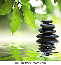 Zen stones pyramid on water surface - Grean leaves over zen...