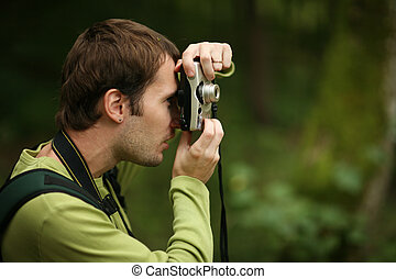 Photographer shooting with compact camera in forest. Shallow...